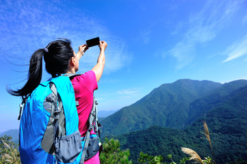 hiking woman taking self photo at mountain peak