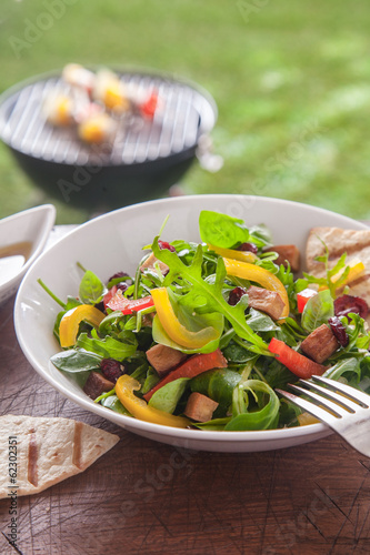 Fresh healthy herb salad on a picnic table