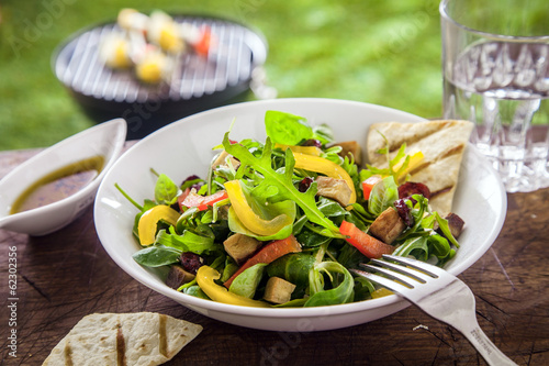 Tasty herb salad on a summer picnic table