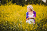 young girl standing in yellow flowers meadow