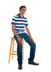 Full body indian man sitting on a chair over white background