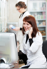 Pharmacy chemist women in drugstore with phone