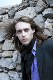 Portrait of a young man with long hair near a stone wall