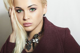 Beautiful Blond Woman in Topcoat. Fashionable Girl with Jewelry