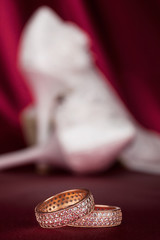 Wedding rings on the background pair of shoes
