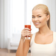 smiling woman holding glass of tomato juice