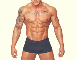 Torso of a naked tattooed bodybuilder