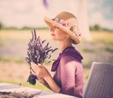 Woman in purple dress and hat behind table in lavender field