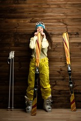 Happy woman with skis and ski boots near wooden wall