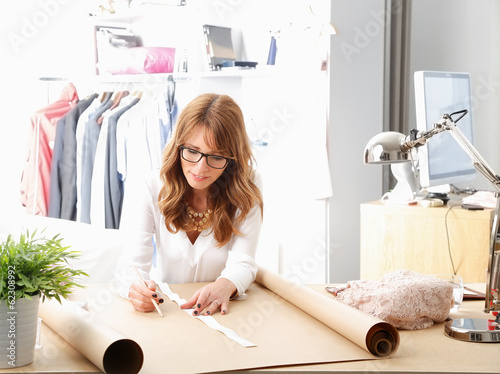 Beautiful fashion designer working in her studio