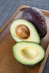 Ripe avocado on wooden plate. Closeup.