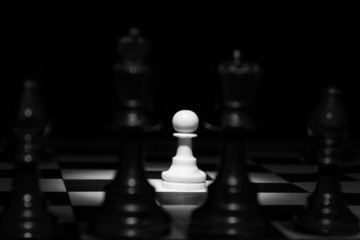 White pawn standing alone in spotlight on chess board with black