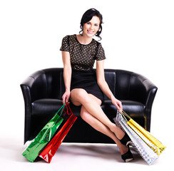 Elegant woman in black dress with shopping bags.