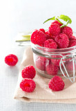 Fresh raspberries in a jar on the table close-up.