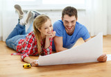 smiling couple looking at blueprint at home