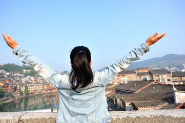 cheering woman tourist open arms at fenghuang ancient town