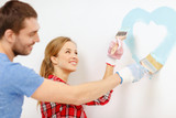 smiling couple painting small heart on wall