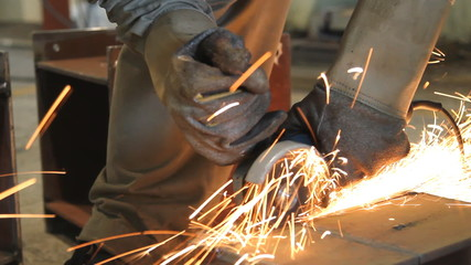 Industrial Worker cutting steel metal with grinder.