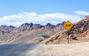 scenic road Artists Drive in Death valley with road sign DIP for