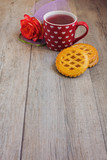 Tea cup and cookies over wooden table