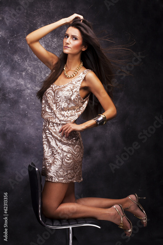 Beautiful young woman on abstract gray background.