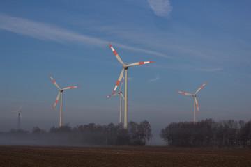 Windräder in nebeliger Landschaft