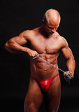 Muscular male bodybuilder posing in studio