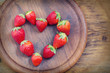 Strawberries with heart shape on wooden board
