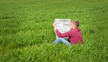 man reading a newspaper outdoors