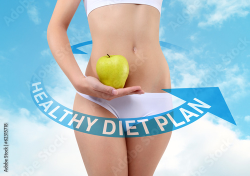 woman holding an apple with hands near the belly, diet concept