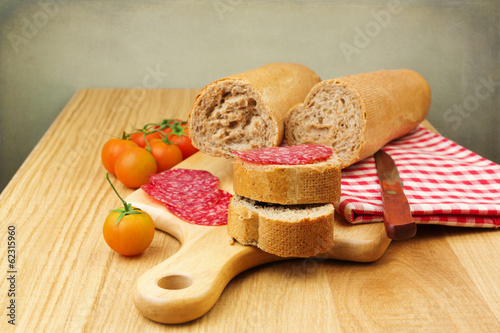 Bread with sliced meat sausage salami and tomatoes