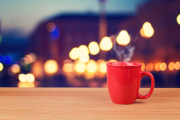 Red cup over city bokeh background