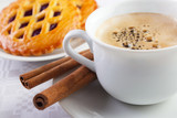 Coffee cup with cinnamon sticks and berry pie