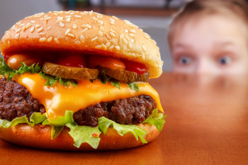 Hungry young boy is staring beef burger on table