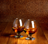Two goblets of brandy on wooden old counter top