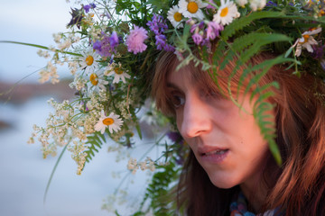 Beautiful Girl with summer bouquet and  wreath of grass.