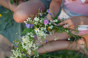 Girls make summer bouquet with grass and flowers.