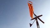 Orange wind sock and turbine rotate on blue sky background.