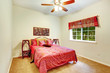 Beautiful bright bedroom with red bedding, french window with re