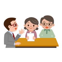 受付に書類を提出するシニア夫婦
