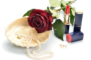 makeup, pearl necklace in the sink and red flower