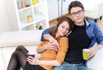 Attractive couple of lovers sitting on a sofa taking a hot drink