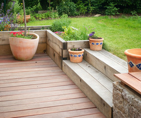 Garden detail with terrace with wooden steps and flowers