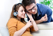 Attractive young couple listening music together in their living