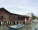 Boat parked next to a stilt home in Chew Jetty Penang