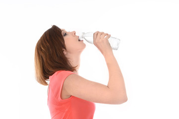 young attractive red hair sport woman drinking water in bottle