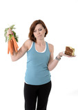 woman holding carrots and cake healthy nutrition concept