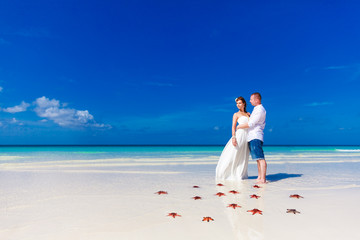 Bride and Groom standing on tropical beach shore with red starfi