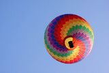 rainbow hot air balloon in a blue sky seen from below.