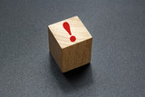 red exclamation mark on wood cube